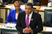 Prime Minister the Most Hon. Andrew Holness speaks in the House of Representatives on Tuesday (June 19). Seated at left is Minister without Portfolio in the Ministry of Finance and the Public Service, Hon. Fayval Williams.